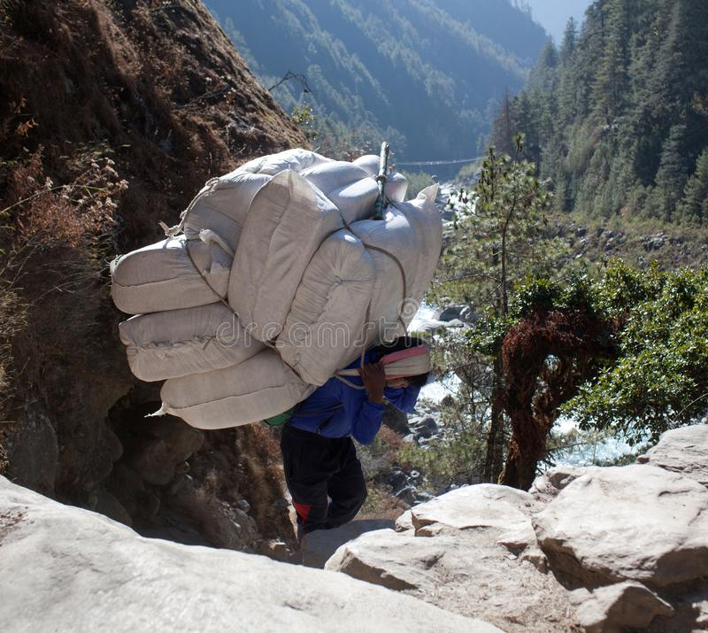 Nepalese porter carrying a heavy load, Nepal Himalayas. NAMCHE BAZAAR, NEPAL - JANUARY 17, 2017: Nepalese porter carrying a heavy load to the pass in Sagarmatha stock photography