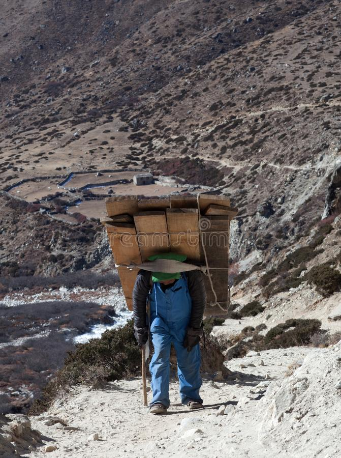 Nepalese porter carrying a heavy load to the pass. DINGBOCHE, NEPAL - JANUARY 13, 2017: Nepalese porter carrying a heavy load to the pass in Sagarmatha National royalty free stock photography