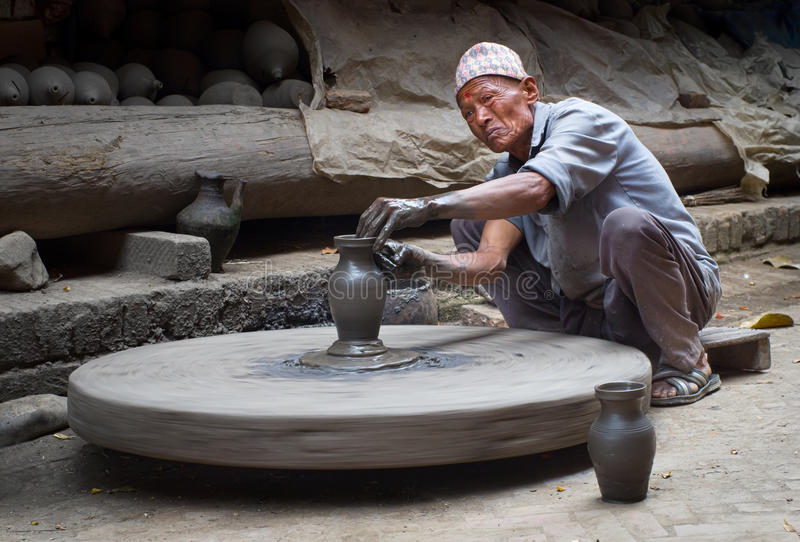 Nepalese potter working in the his pottery workshop. BHAKTAPUR, NEPAL - APR 5: Unidentified Nepalese potter working in the his pottery workshop, Apr 5, 2014 in stock photography