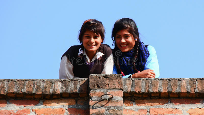 Nepalese students. Two Nepalese students smiling from a brick wall in their school in Kathmandu royalty free stock image