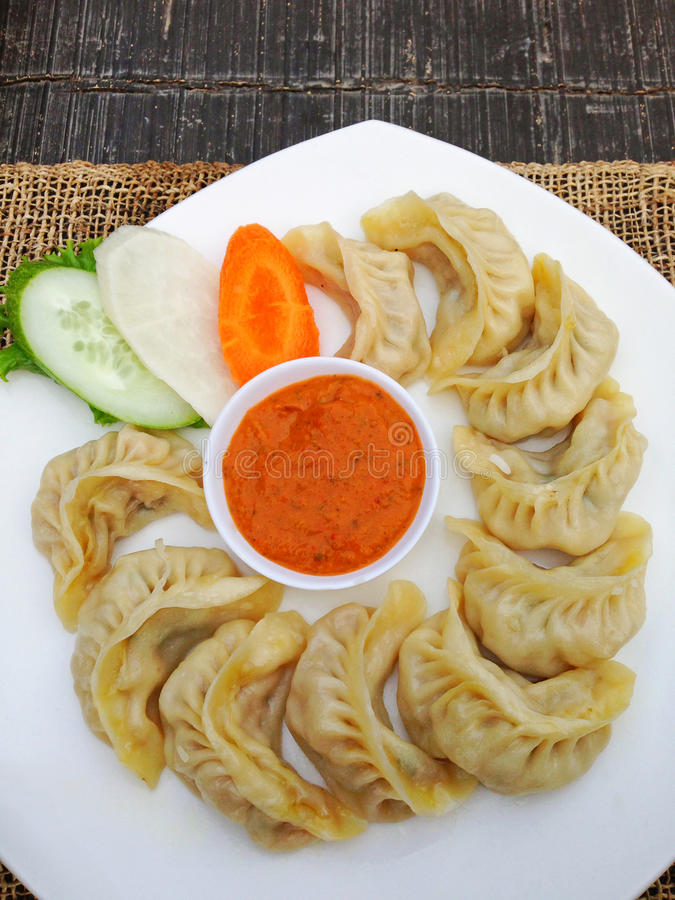 Nepalese and Tibetan traditional dumpling called Momo served wit. Closeup of Nepalese and Tibetan traditional dumpling called Momo served with spicy sauce stock photo
