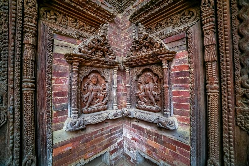 Nepalese traditional style windows with statue of Hindu God on the walls of Patan Durbar Square royalty free stock photo