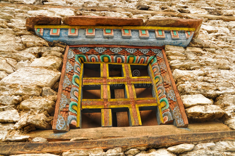 Nepalese window. Traditional decorated window on old stone nepalese house stock images