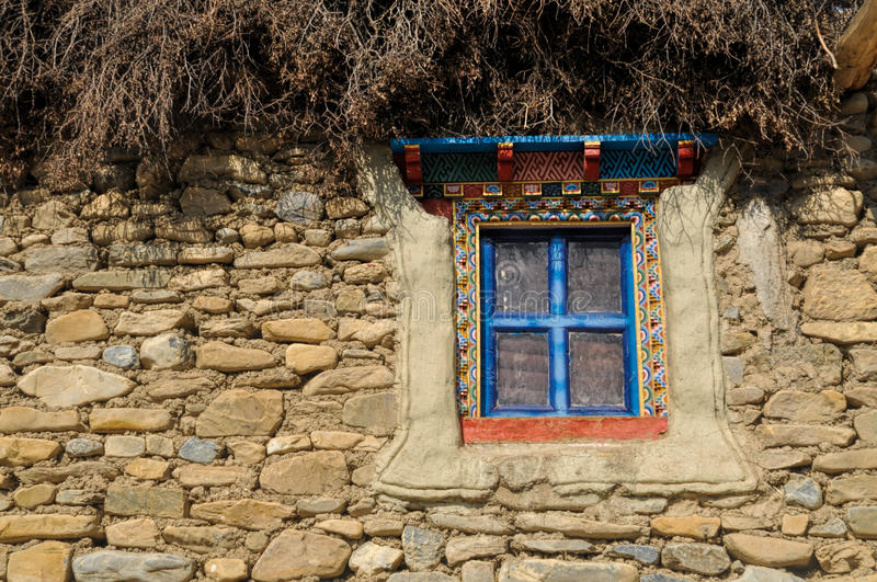 Nepalese window. Traditional decorated window on old stone nepalese house stock photography
