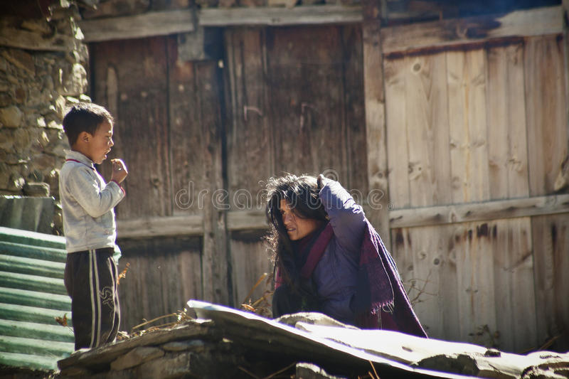 Nepalese woman and boy. Working near their house on the Annapurna trail on October 18, 20130 in Manang, Nepal. Majority of the local population are descendants royalty free stock image