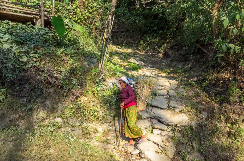 Nepalese woman carrying a basket on her back walking down a rocky footpath. Sekha, Sankhuwasabha District, Nepal - 11/20/2017 : woman worker with basket on her stock photos