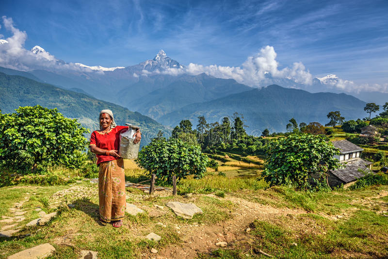 Nepalese woman in front of her home in the Himalayas mountains. DHAMPUS, NEPAL - OCTOBER 27, 2015 : Nepalese woman in front of her home in the Himalayas stock image