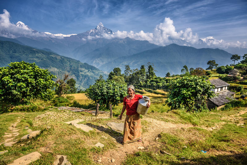 Nepalese woman in front of her home in the Himalayas mountains. DHAMPUS, NEPAL - OCTOBER 27, 2015 : Nepalese woman in front of her home in the Himalayas stock photo