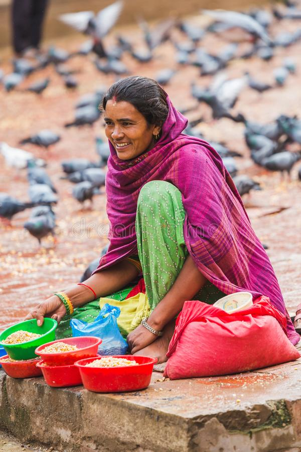 Nepalese Woman Selling Grains For pigeons. Kathmandu,Nepal - Aug 11,2018: Nepalese woman selling grains to the visitors for pigeons at kathmandu durbar square royalty free stock photography