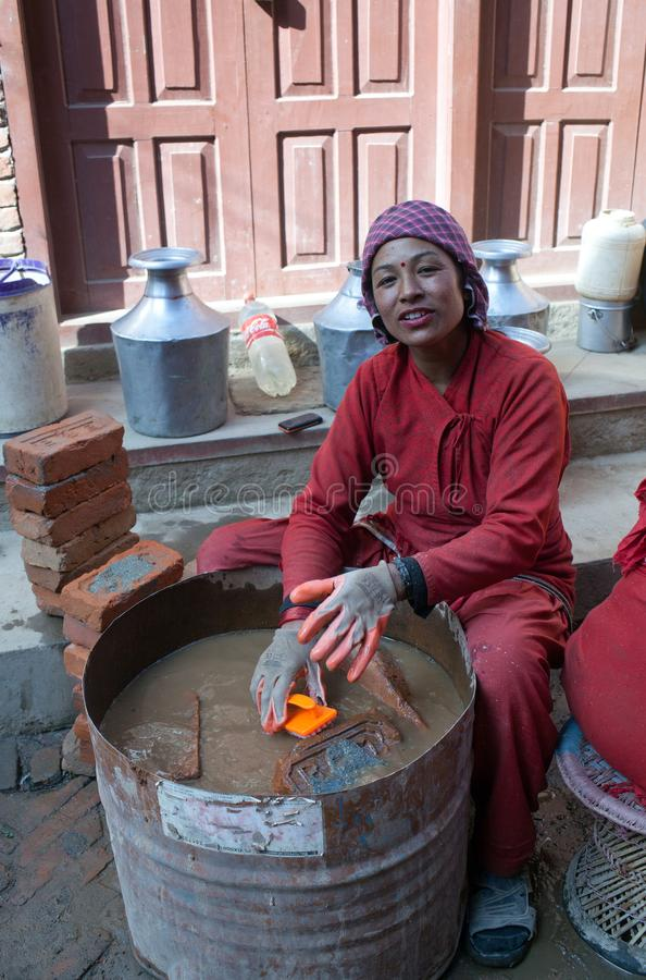 Nepalese woman working hard in building site. BHAKTAPUR, NEPAL - JANUARY 23, 2017: Smiling Nepalese woman working hard in building after the earthquake damage in royalty free stock photography