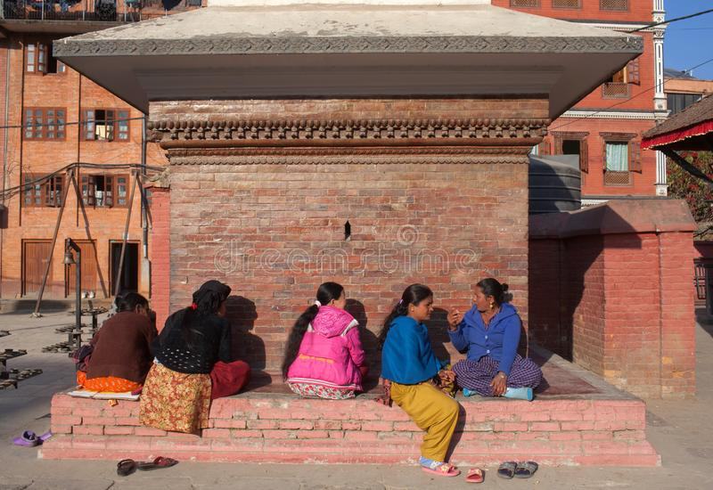 Nepalese women chat together in Patan, Nepal. PATAN, NEPAL - JANUARY 22, 2017: Nepalese women chat together at hindu temple on Durbar square royalty free stock photo