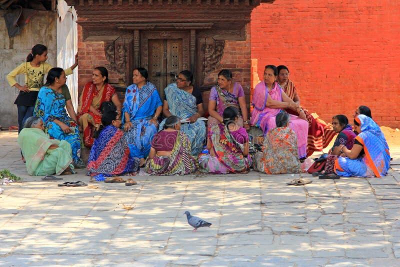 Nepalesische Frauen in ihrem traditionellen Sari kleiden das Sitzen vor Taleju-Tempel stockbild