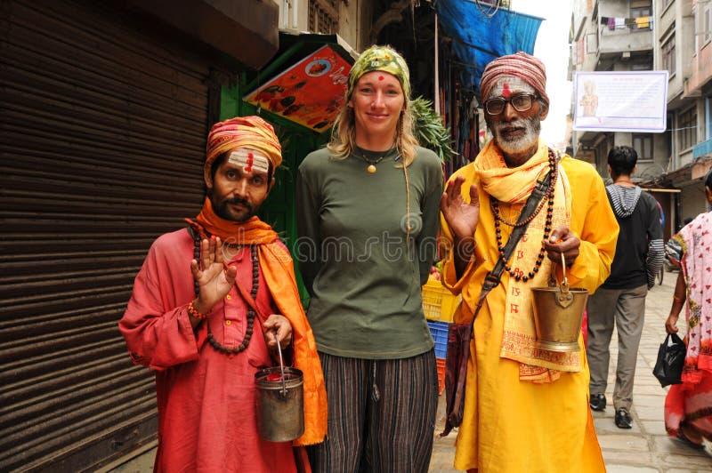 Nepalesische heilige Männer mit blondem Touristen, Nepal stockfotografie