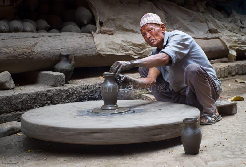 Nepalesischer Töpfer, der in der seiner Tonwarenwerkstatt arbeitet stockfotografie