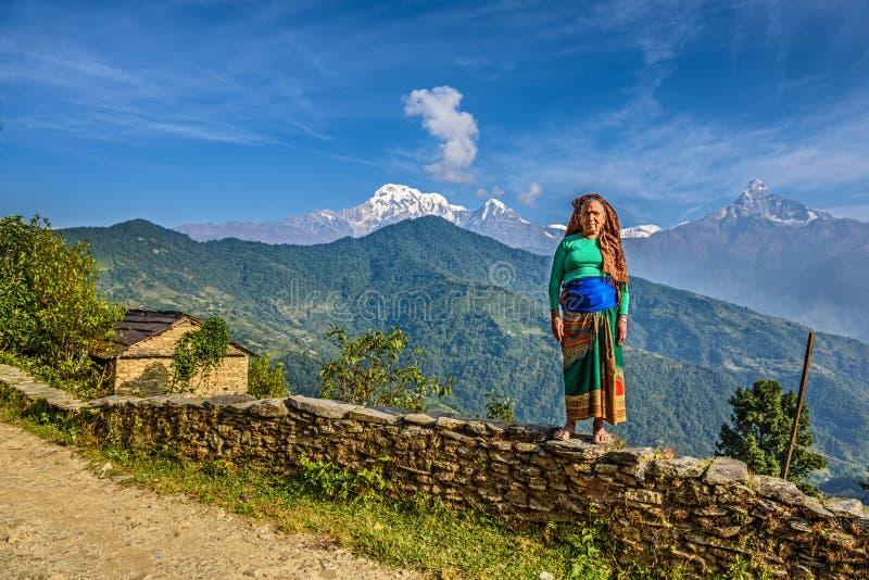 Nepalesisk kvinna framme av henne hem i Himalayasbergen arkivbilder