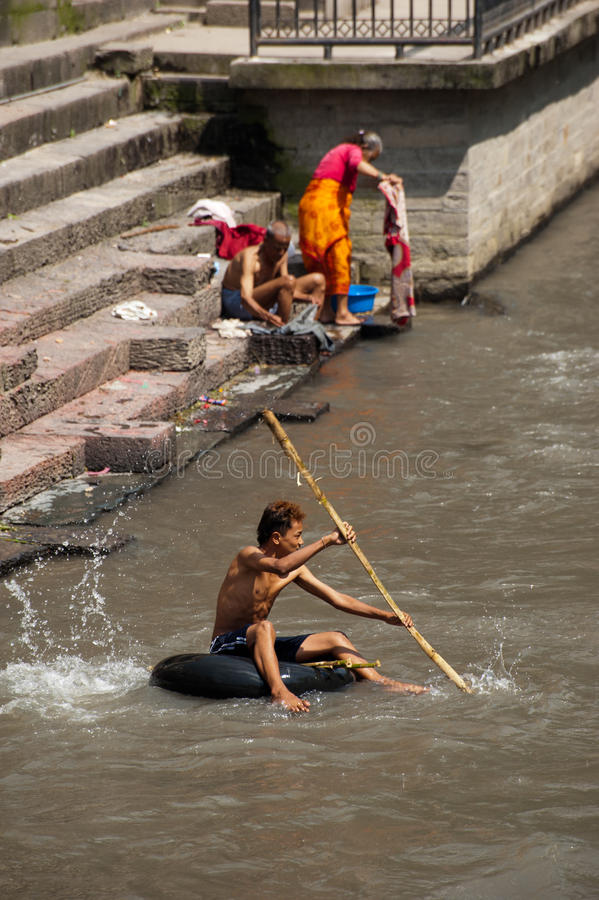 Nepali people at Pashupatinath temple. Nepal, Kathmandu. KATHMANDU, NEPAL - SEPTEMBER 21: Nepali people washing clothes and swimming at holy Bagmati River during stock images