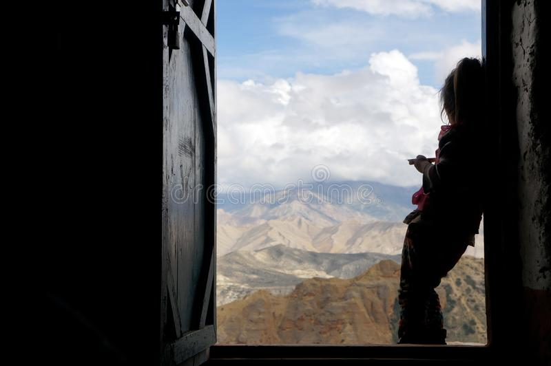 Nepalscy girlie stojaki przeciw tłu spojrzenia przy Himalajskimi górami i drzwi obrazy stock