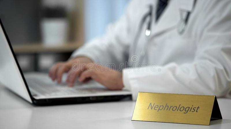 Nephrologist que termina o formulário da referência para o ultrassom do rim, escrevendo o diagnóstico fotos de stock