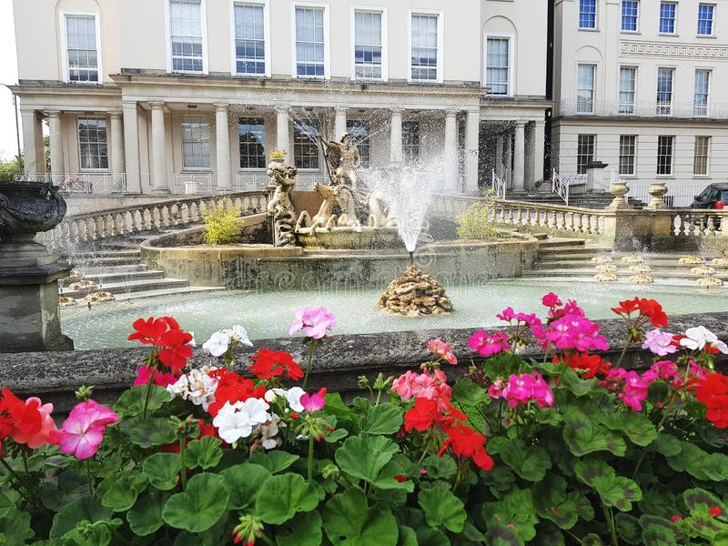 Neptune Fountain in Cheltenham, United Kingdom. Flowers, column, place, water, town stock photos