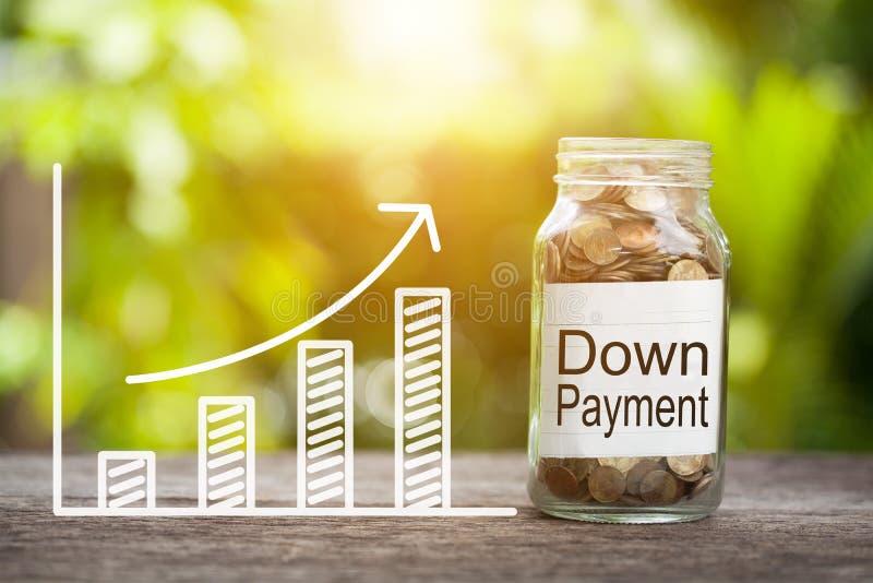 Ner - betalningord med myntet i exponeringsglaskrus och graf upp finansiellt begrepp royaltyfri bild