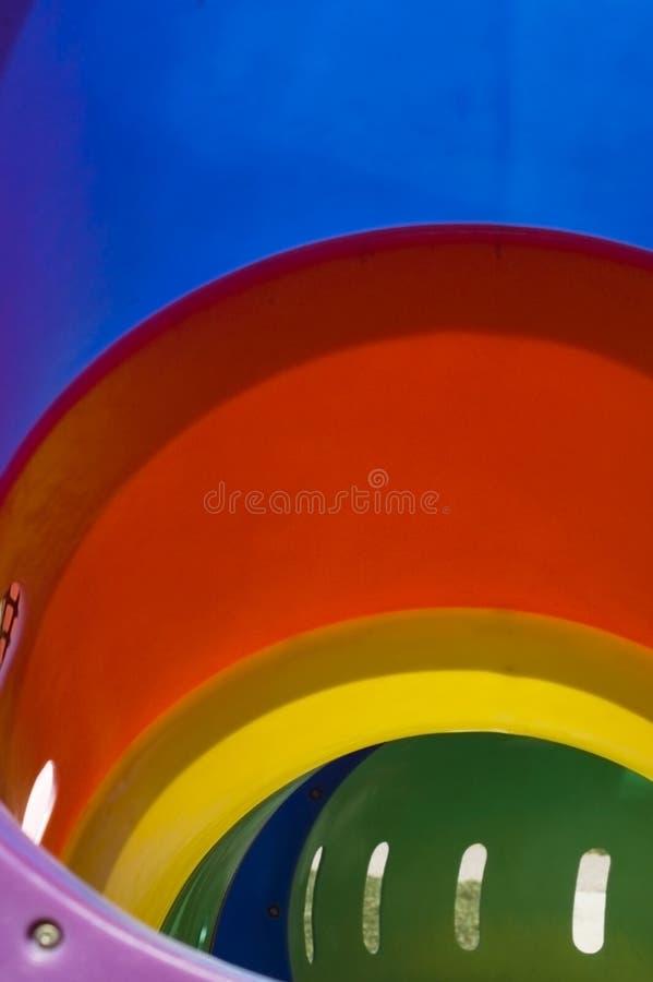 ner regnbågeglidbana arkivbilder