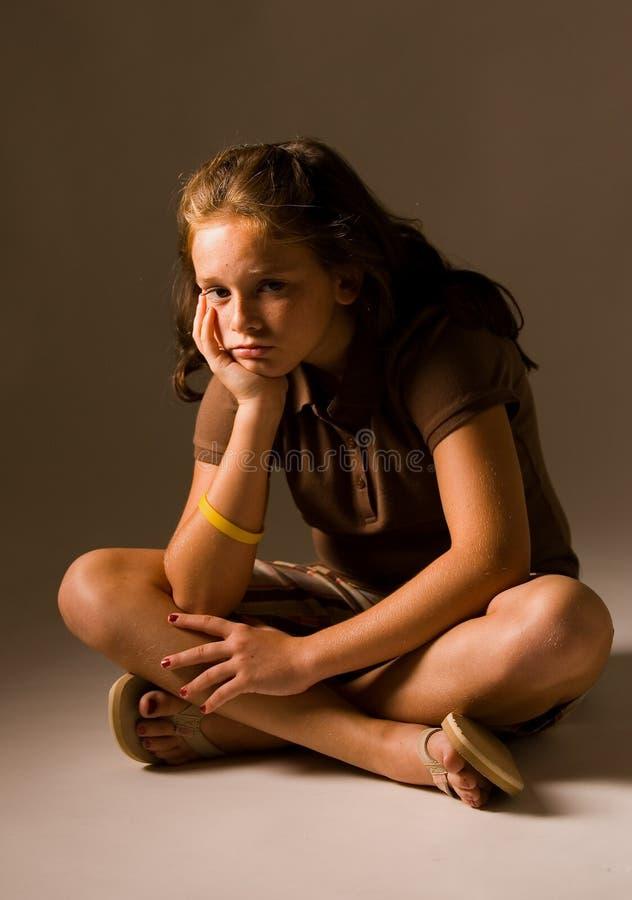 ner SAD sitting för flicka royaltyfria bilder