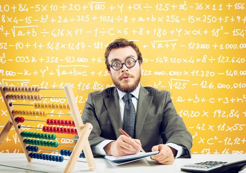 Nerd accountant does calculation of company revenue on yellow background. Nerd accountant does complex calculation of company revenue on yellow background stock photo