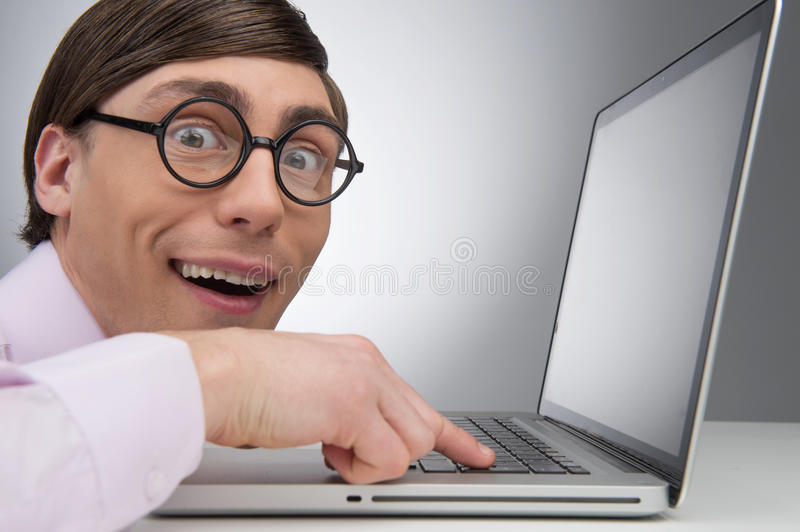 Nerd at the computer. Side view of young nerd man working at the royalty free stock photos