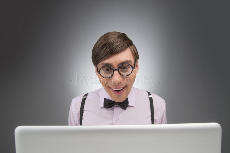 Nerd at the computer. Young nerd man working at the computer while isolated on grey stock image