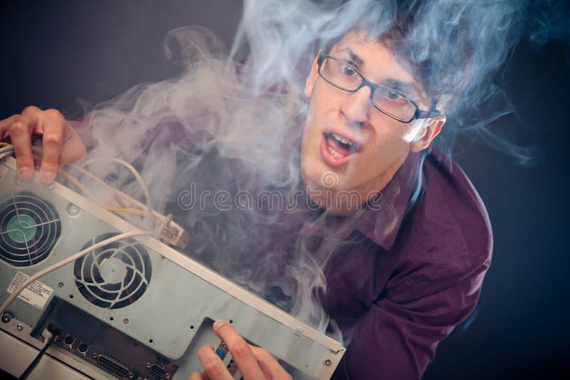 Nerd con fumo che esce dal suo pc fotografie stock libere da diritti