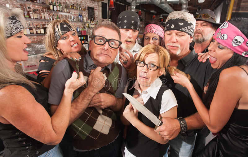 Nerd Couple Mugged by Gang. Biker gang mugging scared nerd couple in bar royalty free stock photography