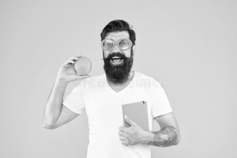 Nerd es el nuevo fresco Hombre nerd con barba Estudiar el libro de los nerds y la fruta naranja sobre fondo amarillo Grabar nerd fotos de archivo