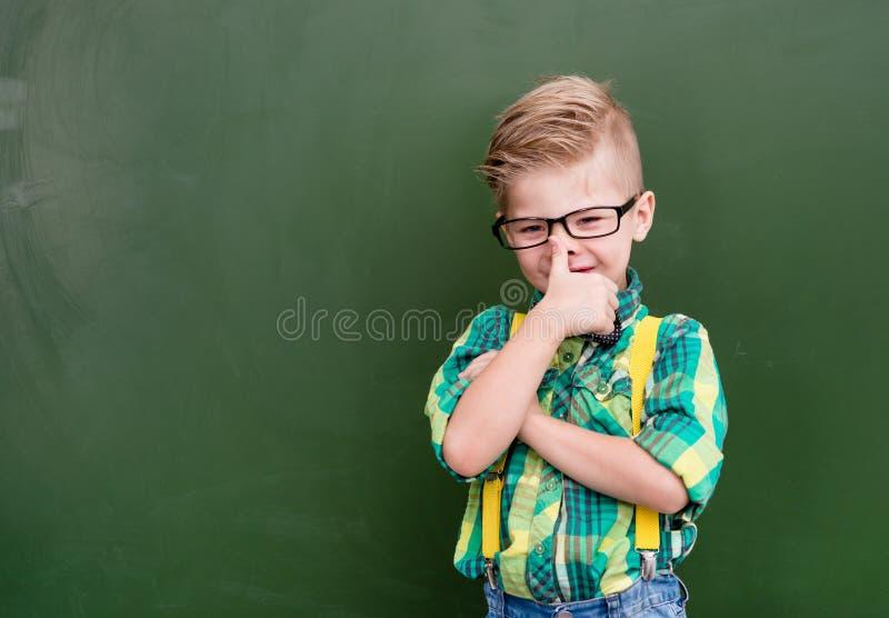 Nerd felice divertente vicino alla lavagna verde vuota immagini stock
