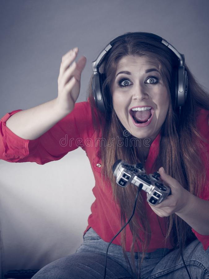 Young woman playing video games. Nerd geek young adult woman playing on the video console holding game pad being shocked Gaming gamers concept stock photos