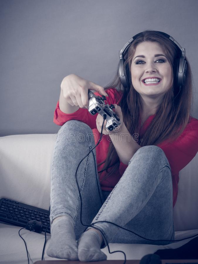 Young woman playing video games. Nerd geek young adult woman playing on the video console holding game pad sitting on sofa. Gaming gamers concept stock photos