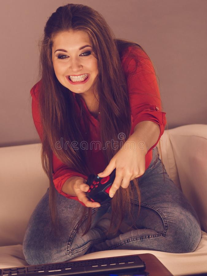 Young woman playing video games. Nerd geek young adult woman playing on the video console holding game pad sitting on sofa. Gaming gamers concept royalty free stock photography