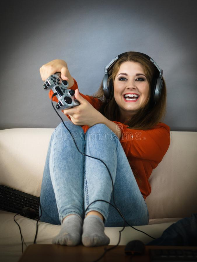 Young woman playing video games. Nerd geek young adult woman playing on the video console holding game pad sitting on sofa. Gaming gamers concept stock images