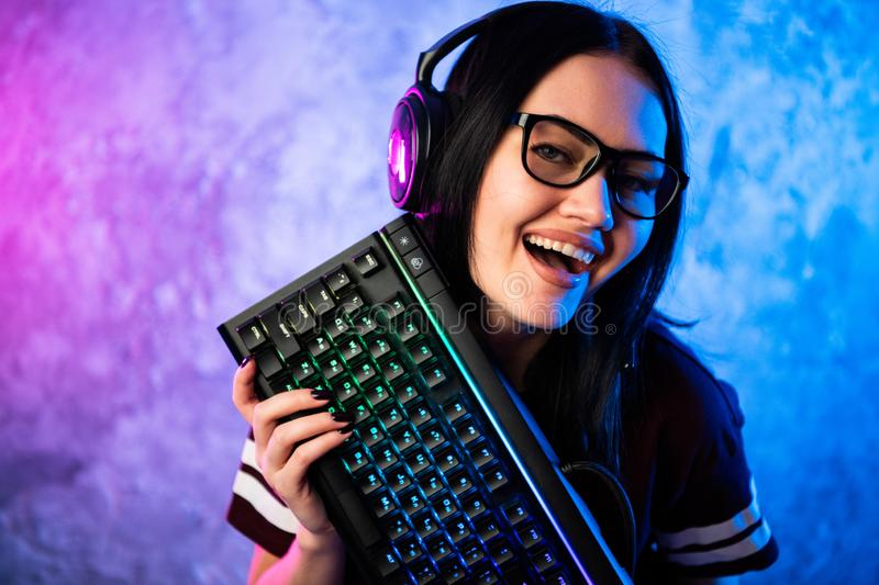 Nerd geek young adult women holding gaming keyboard over colorful pink and blue neon lit wall. Gaming gamers concept. Nerd geek young adult woman playing on the royalty free stock photos