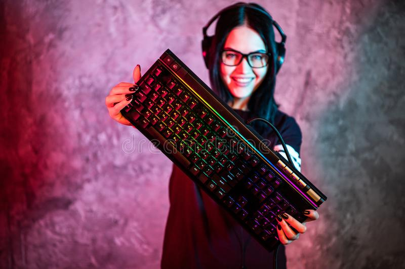 Nerd geek young adult women holding gaming keyboard over colorful pink and blue neon lit wall. Gaming gamers concept. Nerd geek young adult woman playing on the stock photography