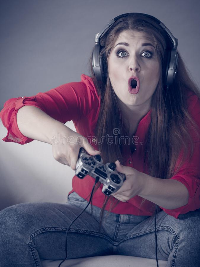 Young woman playing video games. Nerd geek young adult woman playing on the video console holding game pad being shocked Gaming gamers concept royalty free stock photo
