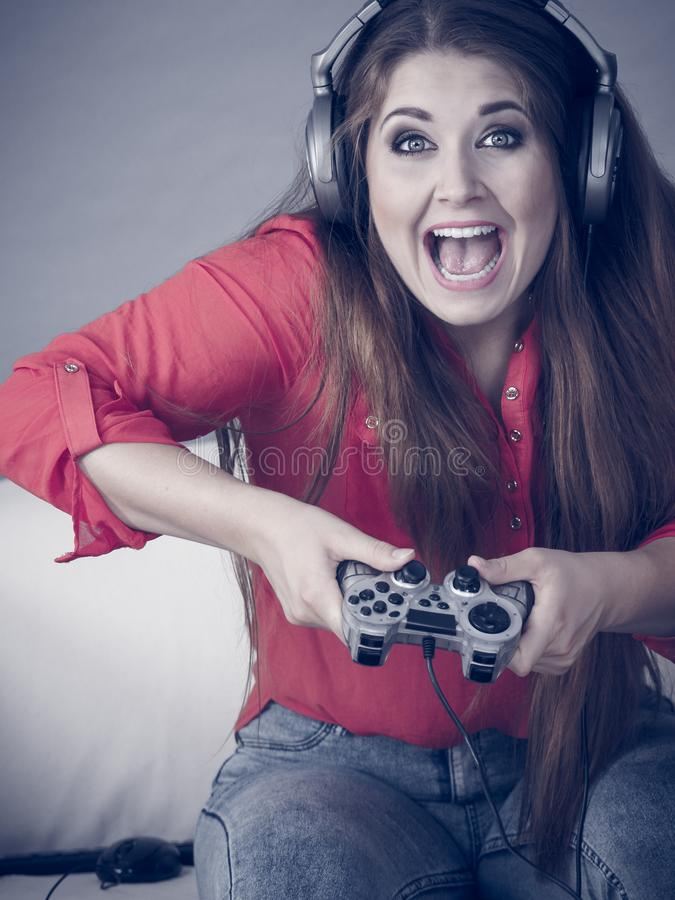 Young woman playing video games. Nerd geek young adult woman playing on the video console holding game pad sitting on sofa. Gaming gamers concept stock image