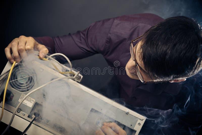 Nerd med rök som kommer ut ur hans PC arkivfoton