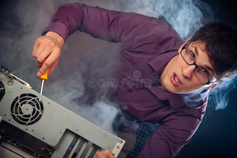 Nerd med rök som kommer ut ur hans PC arkivbilder
