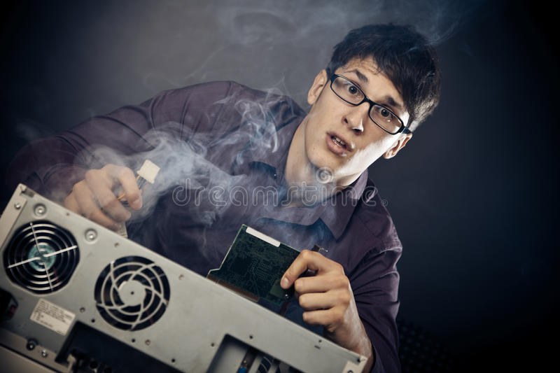 Nerd med rök som kommer ut ur hans PC royaltyfria bilder