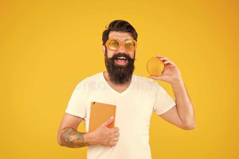 Nerd is the new cool. Bearded nerd man. Study nerd holding book and orange fruit on yellow background. Book nerd in royalty free stock image