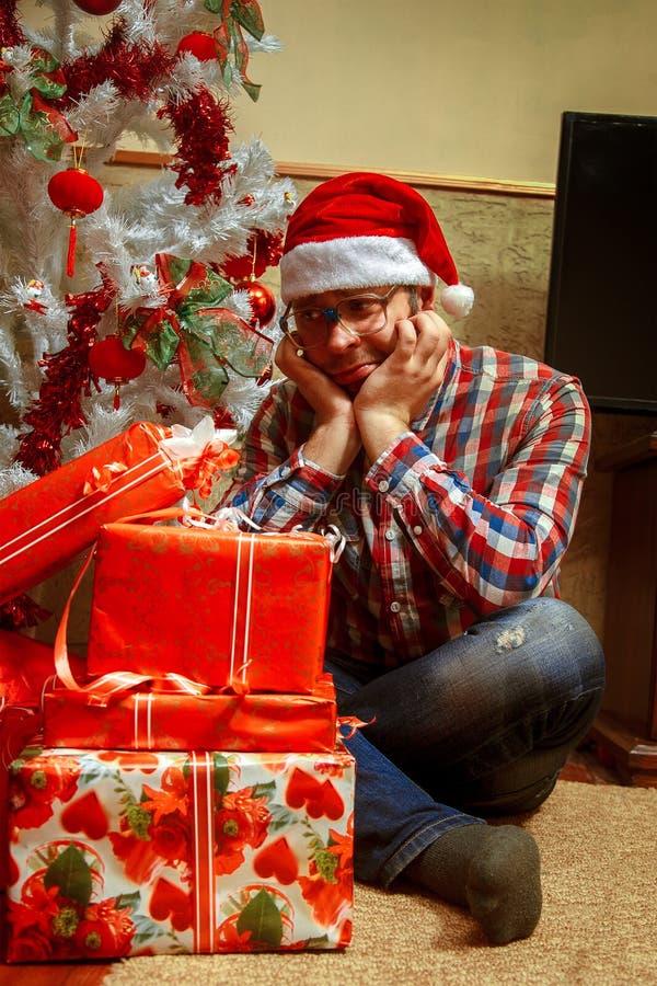 Nerd solo triste con un mazzo di regali di Natale immagini stock libere da diritti