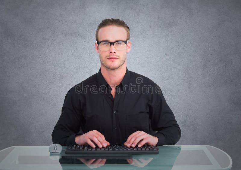 Nerdmens bij bureau tegen grijze muur met grungebekleding stock fotografie