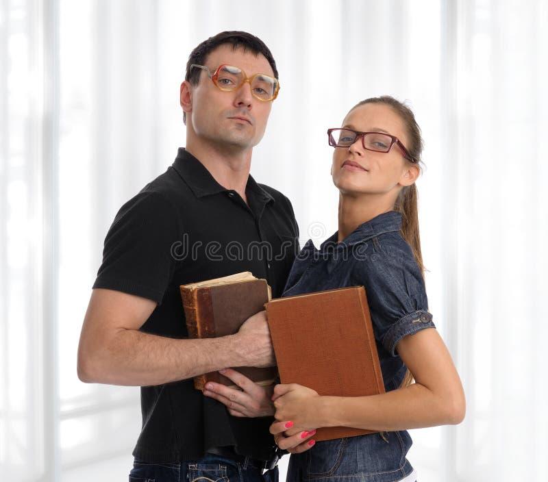Nerdpaar met boeken stock afbeeldingen