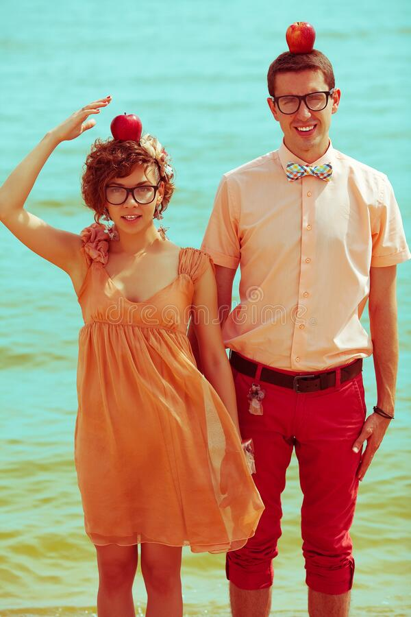 Nerds` honeymoon concept. Portrait of couple of young happy married hipsters in trendy clothes standing together on the beach wit stock photos