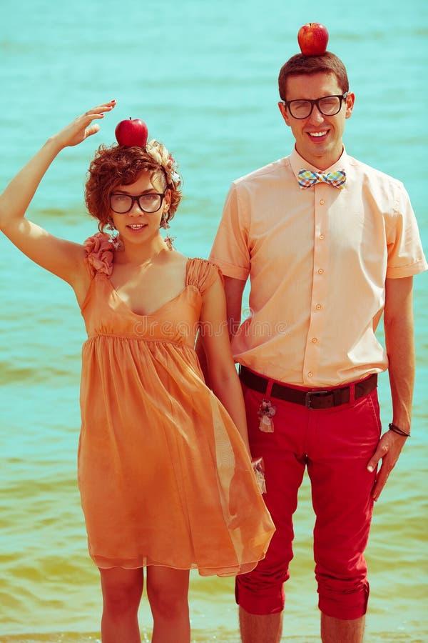 Nerds' smekmånadskoncept Stråldrag av ett par unga lyckliga gifta hipsters i trendiga kläder som står tillsammans på stranden med arkivfoton